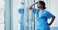 ethical dilemmas - A young female nurse looking stressed out while standing at a window