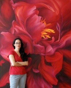 """Valley Burke, RN, stands in front of her painting """"Red Goddess""""."""