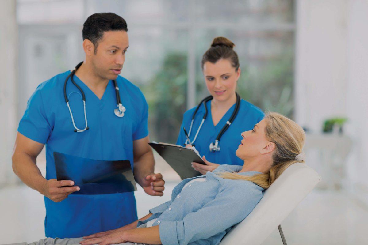 male nurse and female nurse taking care of female patient