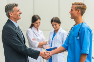 administrator and male nurse shaking hands