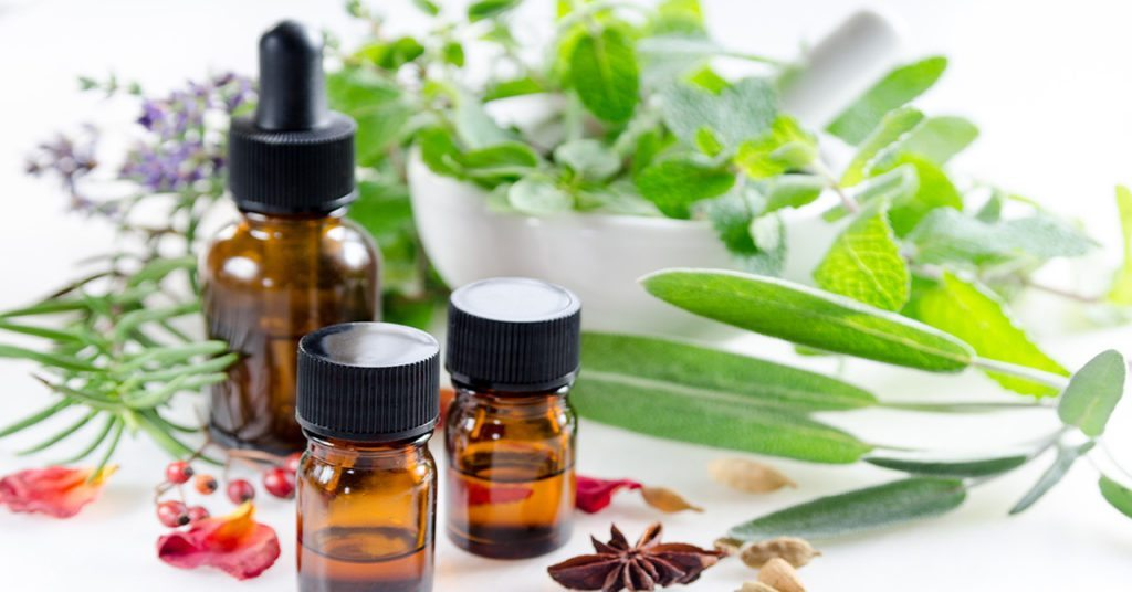 alternative therapy with herbs and essential oils in white background