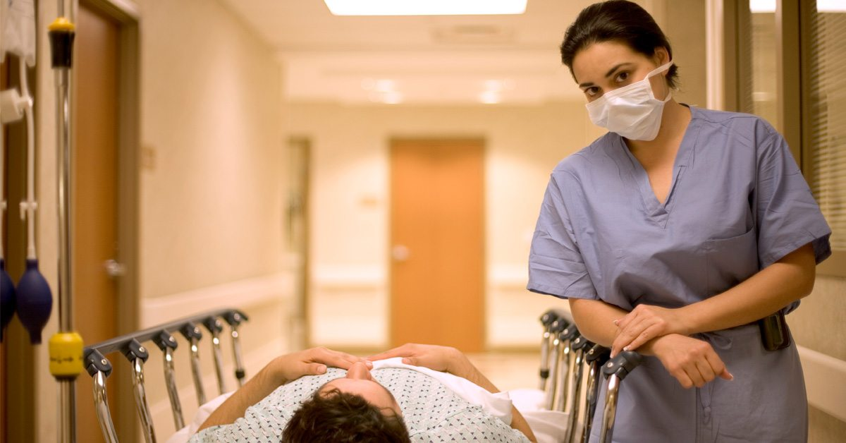 nurse next to patient in a patient bed
