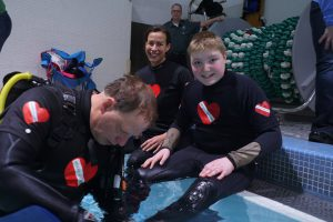 Diveheart staff prep a young participant for a scuba therapy session.