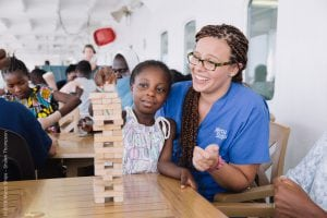 Nurse Hannah Thyberg, BSN, BA, RN and a patient play Jenga together, while enjoying some sunshine and fresh air on Deck 7 of the Africa Mercy. Photo courtesy of Mercy Ships.