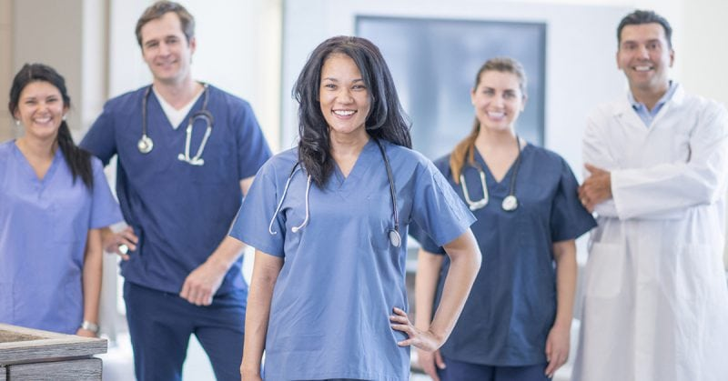 nurse leader - multi-ethnic group of nurses and healthcare professionals wearing scrubs and a lab coat and smiling
