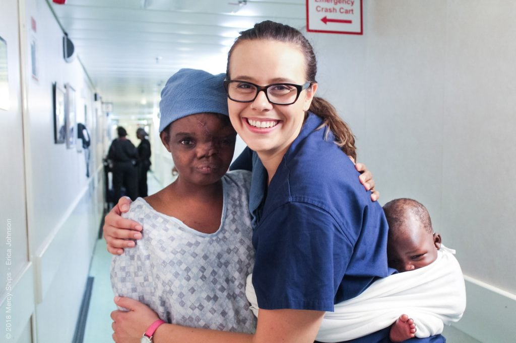 Mercy Ships volunteer Hannah Thyberg, BSN, BA, RN, with two of the floating hospital's patients.