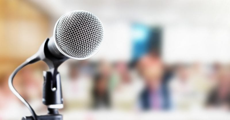mainstream media - A vocal microphone in close up in front of a defocused, seated audience at a meeting, press conference, or seminar.