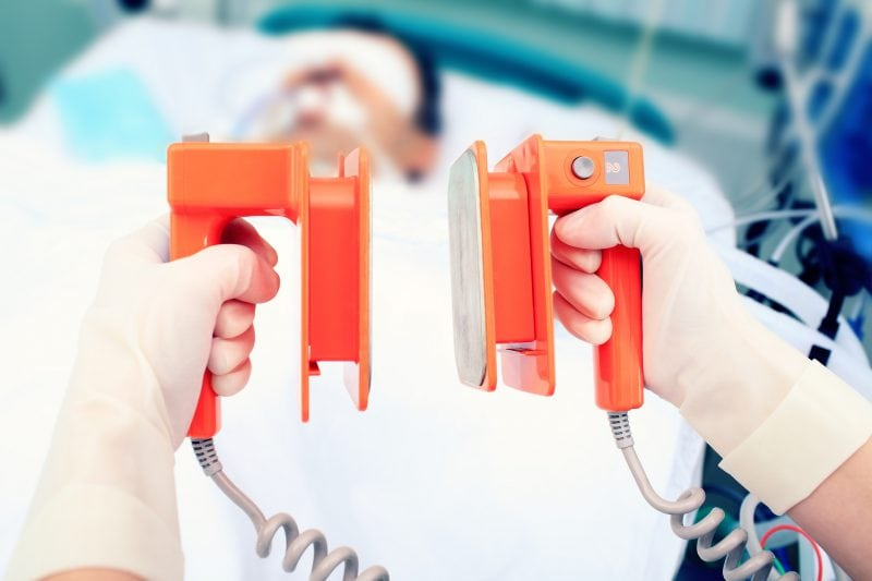 defibrillator electrodes in hands. Work in the ICU and critical care