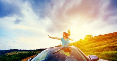 happy woman with arms raised in the car, enjoying her vacation, laughing and having fun.photo taken at sunset.