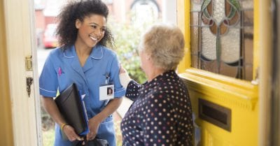 home health - A female nurse or community care worker is at the front door of her senior female patient and saying hello. She is wearing a blue nurses tunic , and holding a medicines bag .