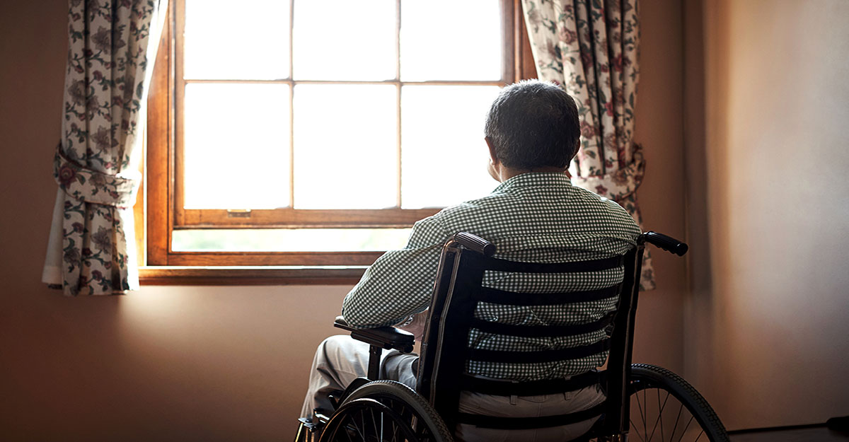 nursing home abuse - Rearview shot of a senior man looking out the window while sitting in his wheelchair