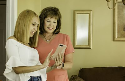 nurse-family partnership - Kathy Pounds, RN, shows new mom how to use Goal Mama app.