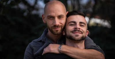 lgbtq healthcare - gay couple embracing outdoors.