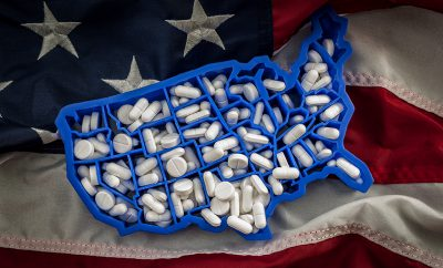 opioid epidemic - Healthcare, opioid epidemic and drug abuse concept with the map of USA filled with oxycodone and hydrocodone pharmaceutical pills on the American flag