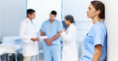moral distress - Tired or stressed nurse leaning against a wall with colleagues in the background.