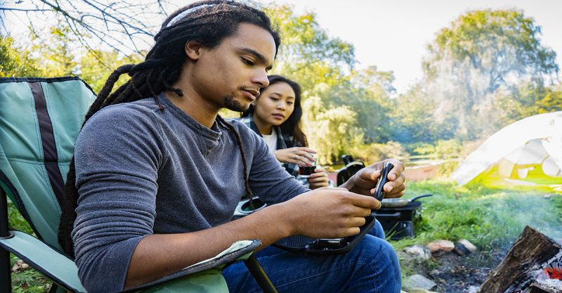 diabetes education - Young African American man with diabetes checking his blood sugar at a campsite in the woods. His girlfriend is lending her support.