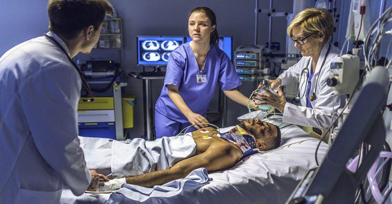 emergency nurses - Female nurse and doctors working on patient in emergency room.